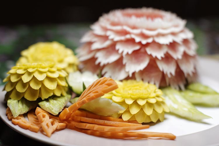 Finished fruit carving design consisting of watermelon and pumpkin flowers, and carrot leaves.