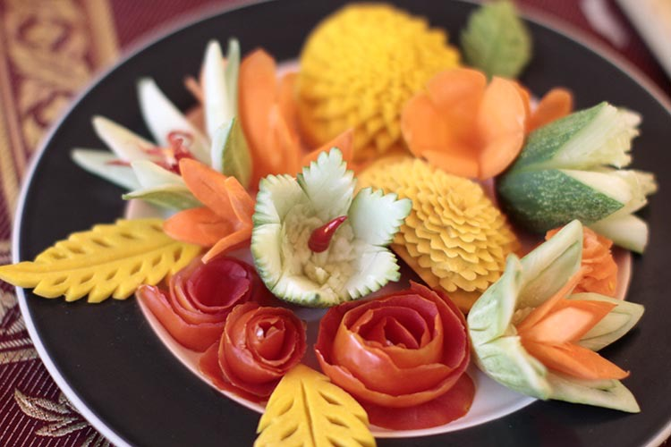A black and white plate with a variety of finished fruit carvings including yellow leaves carved from Thai pumpkin, yellow carnations carved from Thai pumpkin, orange flower pedals carved from carrots, roses carved from tomatoes, and white flowers carved from cucumbers with red chilis to represent the stamens.