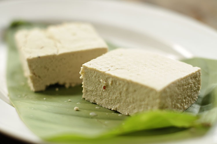 Two freshly made cut blocks of tofu placed on a banana leaf on a white plate.
