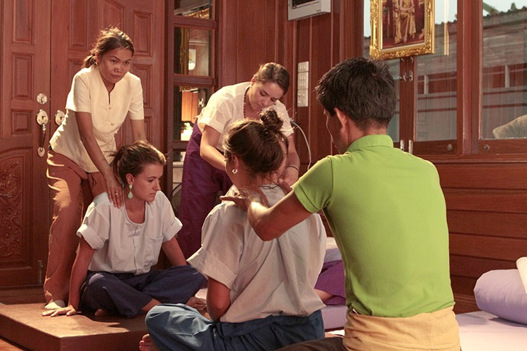 Three students learning beginning Thai massage techniques from two instructors. One instruction wearing a green shirt is applying pressure to the shoulders of a student seated cross-legged. The student faces two other students, one of who is receiving similar techniques to the shoulders by the other instructor, and the third student receiving the same from another student.