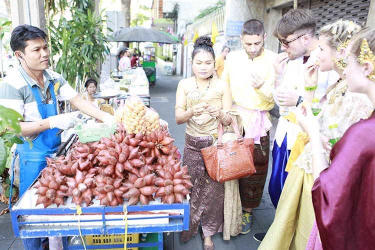 Students and instructor sampling the tropical fruit known as salak as a fruit vendor wearing a blue apron looks on. There is a matching blue pushcart with a large pile of salak fruit sitting on top, an abundance Thai vegan nourishment.