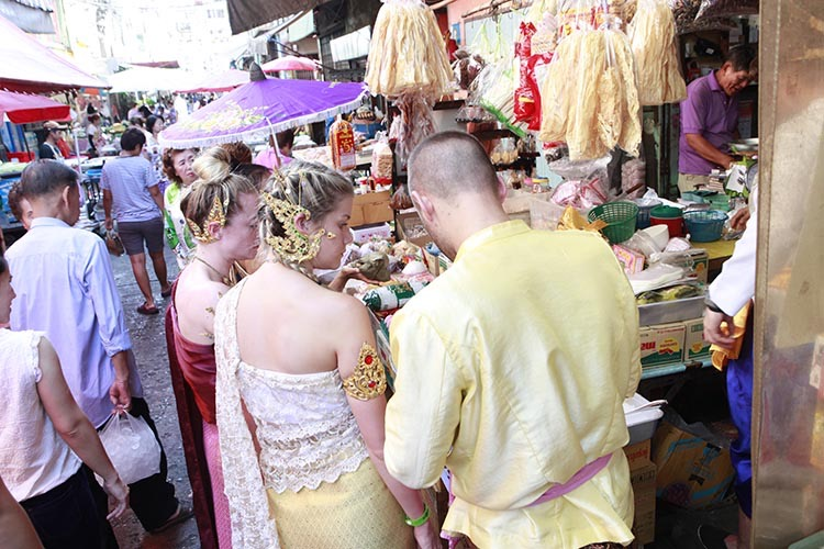 Students wearing traditional Thai dress huddle around a vendor's table at the local open air market, examining items like sticky rice wrapped in banana leaves and coconut custard.