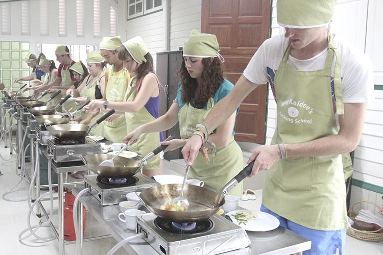 A row of students wearing light green aprons and headscarves  cooking in the classroom with stainless steel woks and spatulas on gas burners. Students are cooking Thai vegan recipes from May Kaidee's popular Thai cooking recipe set.