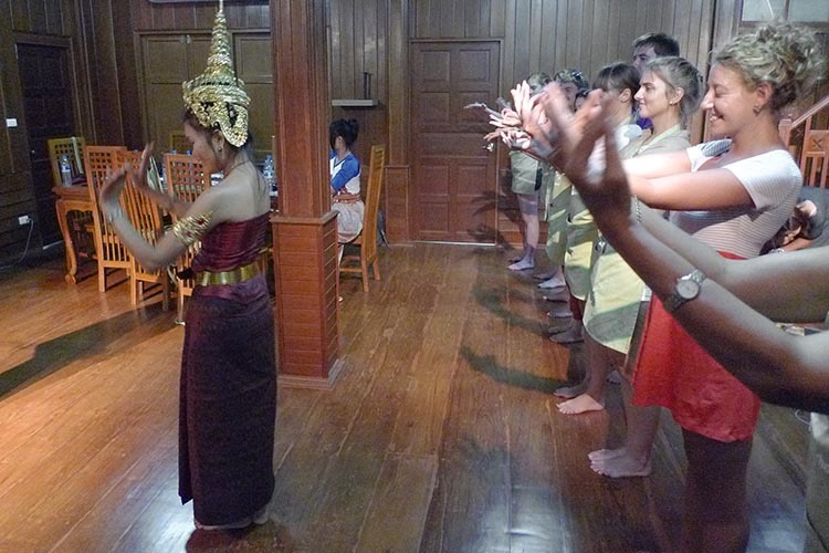 Students standing in a row being led by the instructor learning the beginning steps of traditional Thai dance. The instructor is wearing a traditional style Thai crown and belt.
