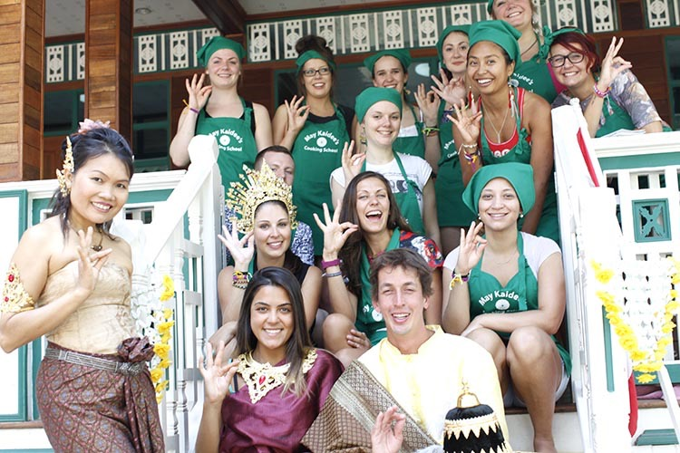 Instructor standing next to students, some wearing green aprons while others wear traditional Thai dress, seated in rows on the steps of the cooking school positioning their hands in gestures used during Thai dancing.