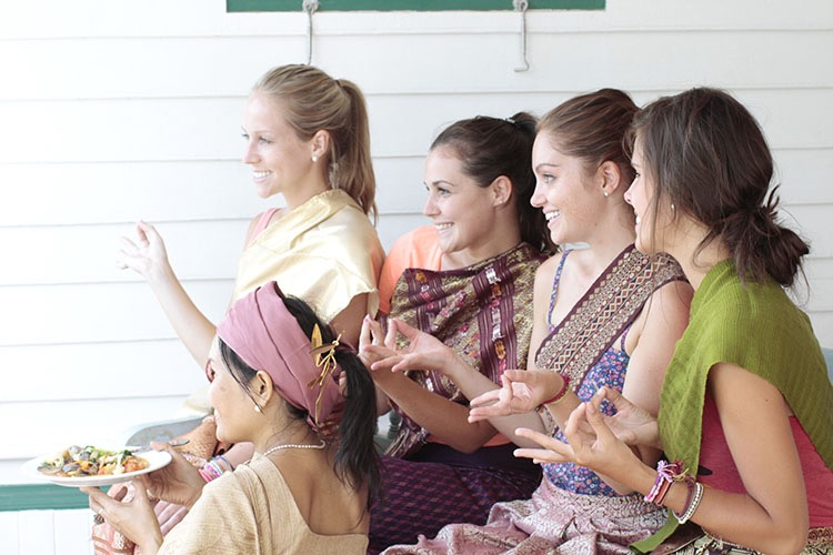 Students posing for a photo wearing traditional Thai dress while their instructor holds a vegan Pad Thai noodle dish they made during the cooking instruction portion of the Thai culture and cooking class.