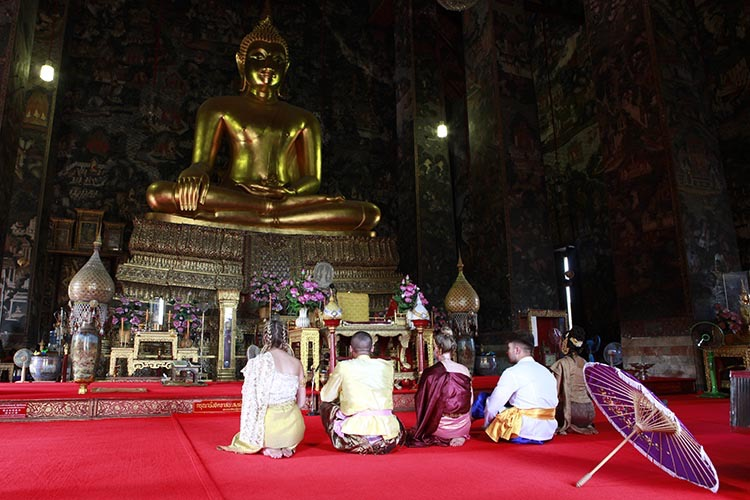 Four students wearing traditional thai dress and an instructor seated on a red carpet inside the temple in front of a giant golden Buddha statue with flowers in front of it. A purple parasol sits in the foreground.
