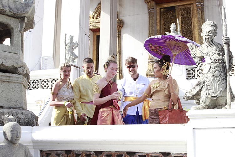 Students wearing traditional Thai dress and costume, standing outside a temple surrounded by statues with their instructor holding a purple parasol.
