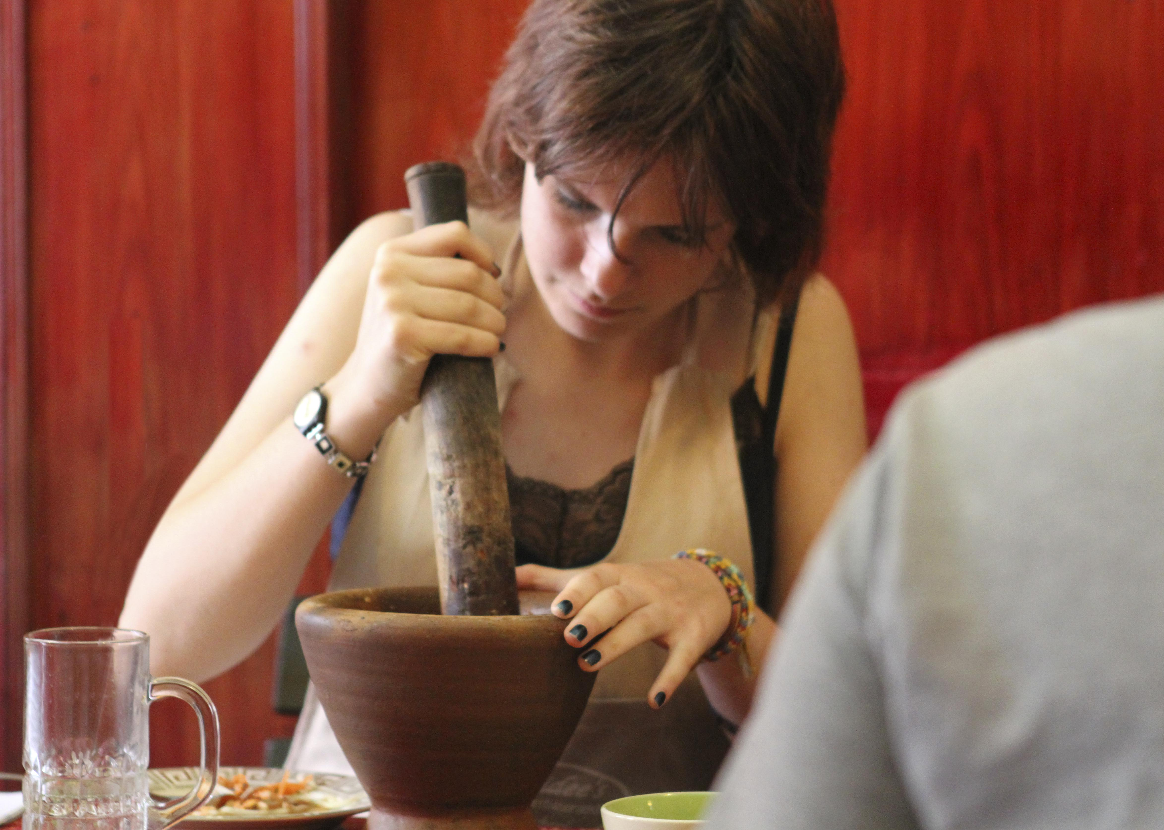 Cooking class student making chili paste with a mortar and pestle.