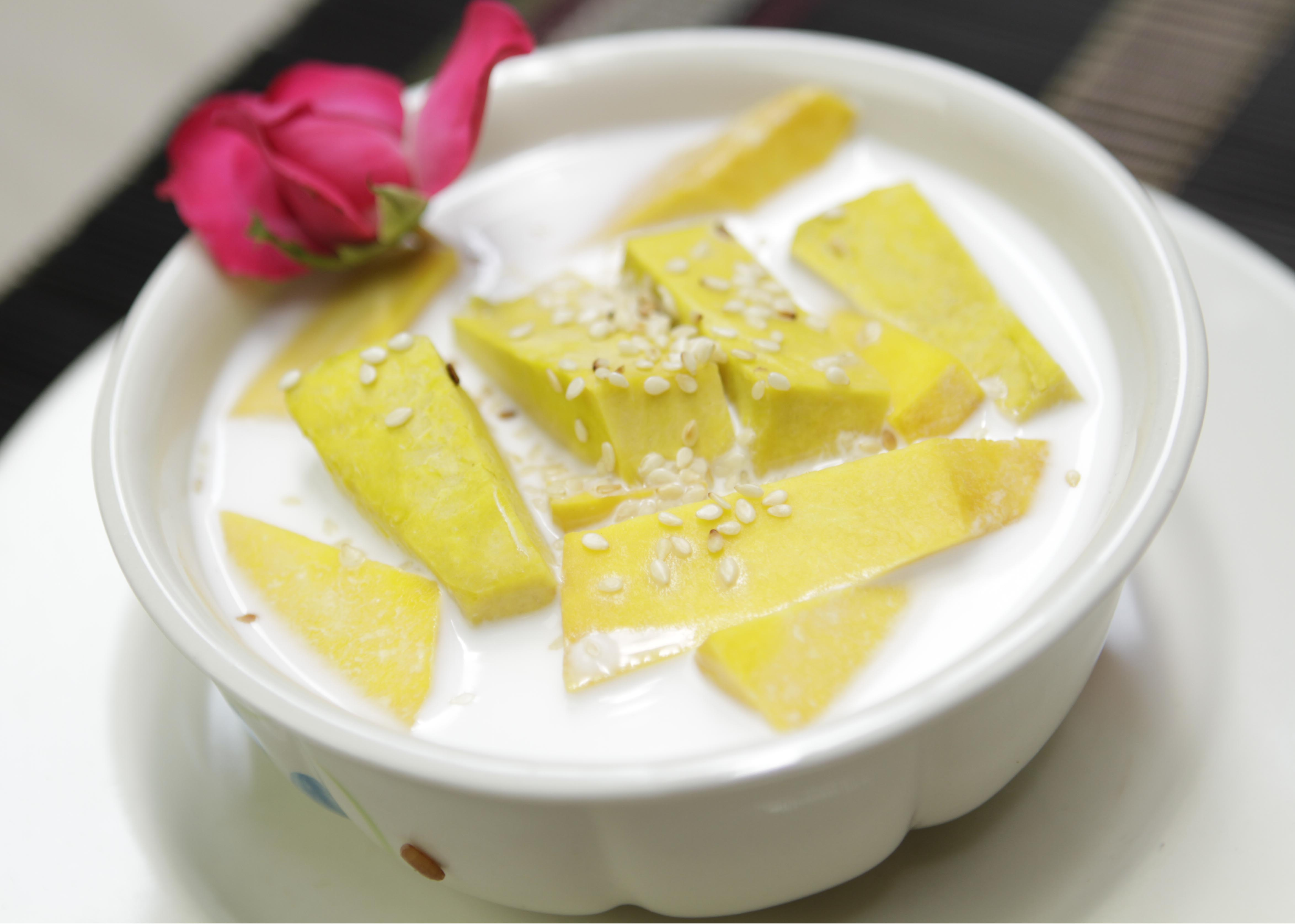 Steamed pumpkin slices in sweet coconut milk dessert, topped with sesame seeds and a pink rose as garnish.