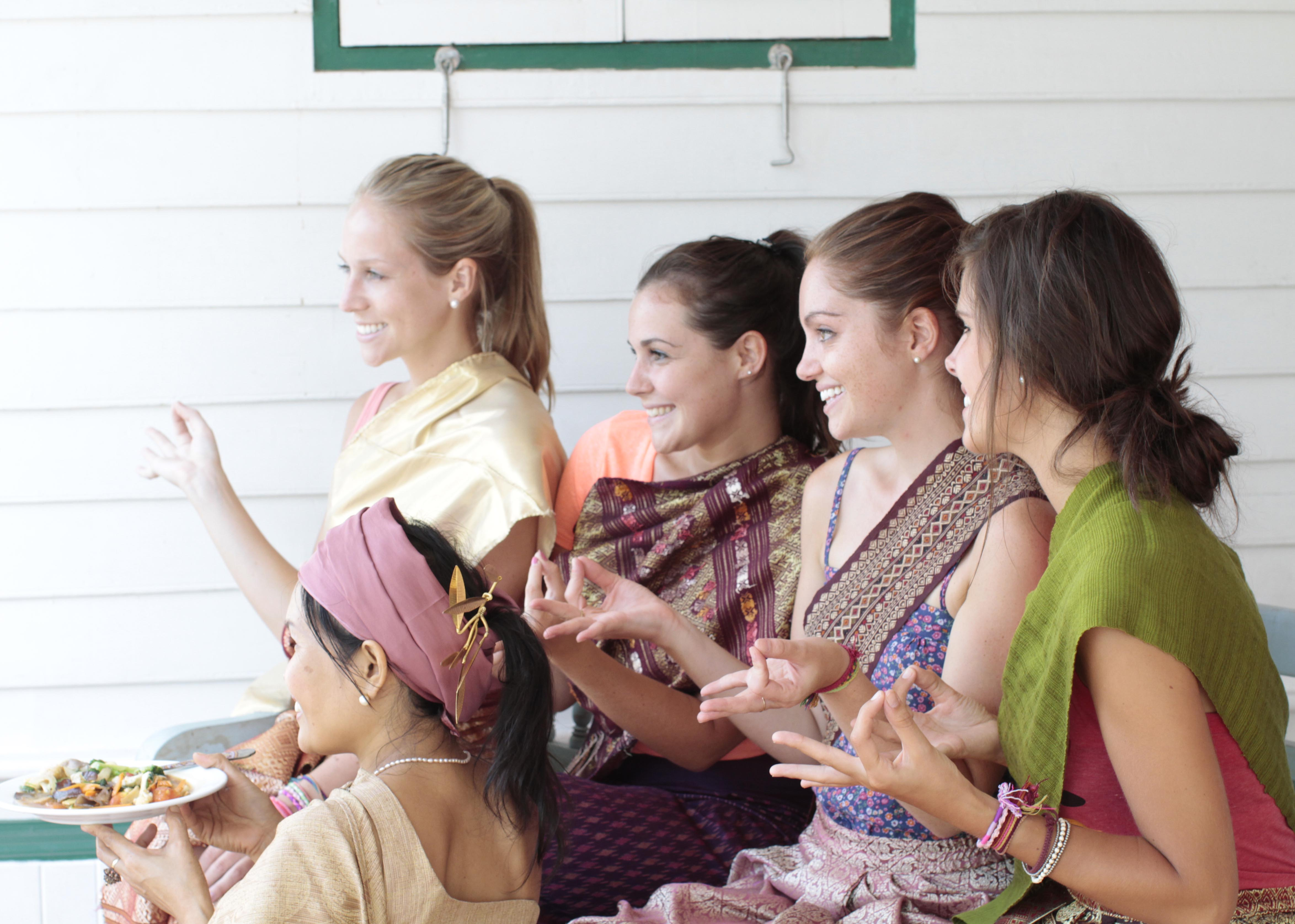 4 women students wearing Thai dress posing with May the founder after a cooking class in Bangkok, Thailand.