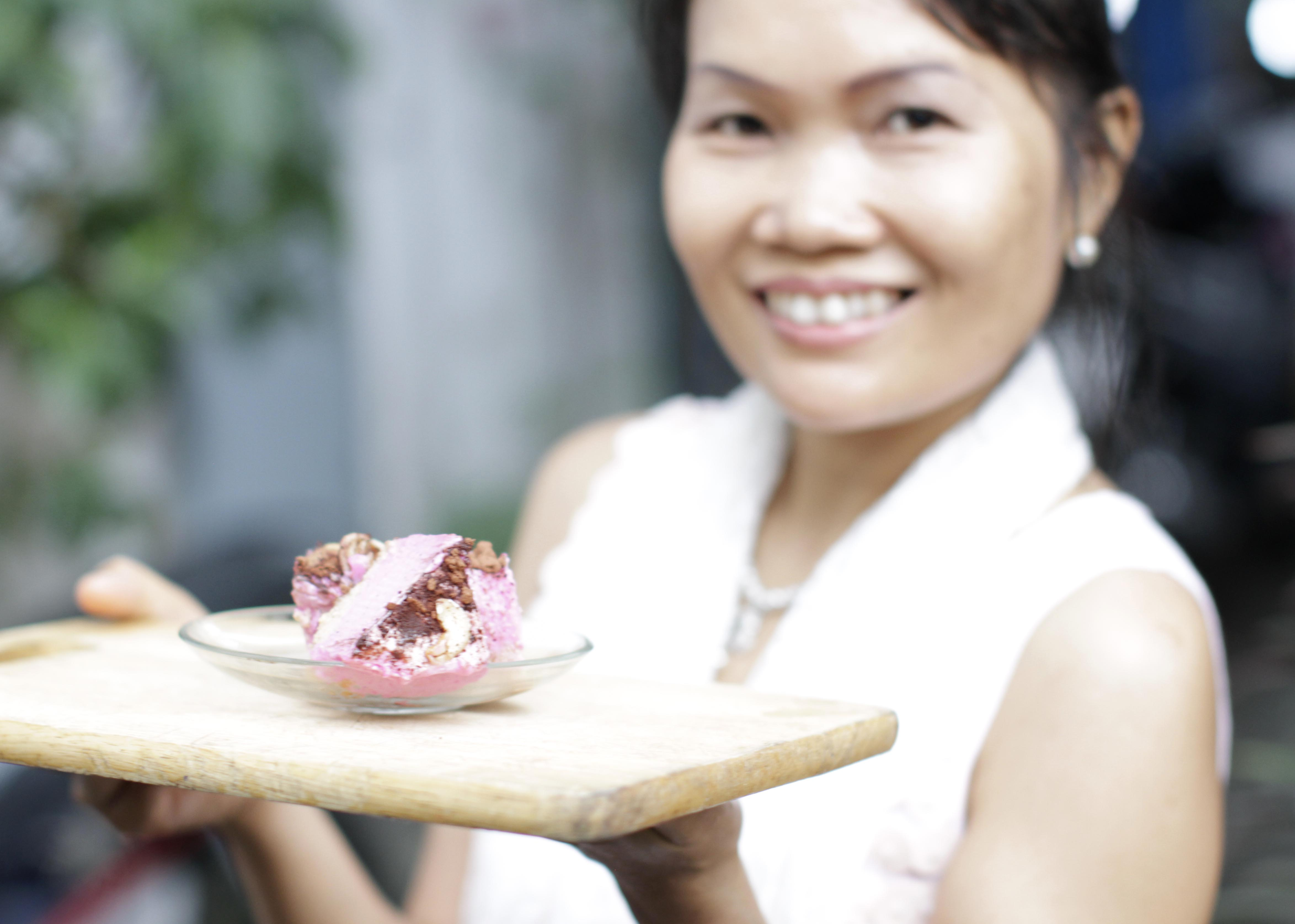 Our founder May holiding a plate of vegan magenta dragonfruit ice cream cake.